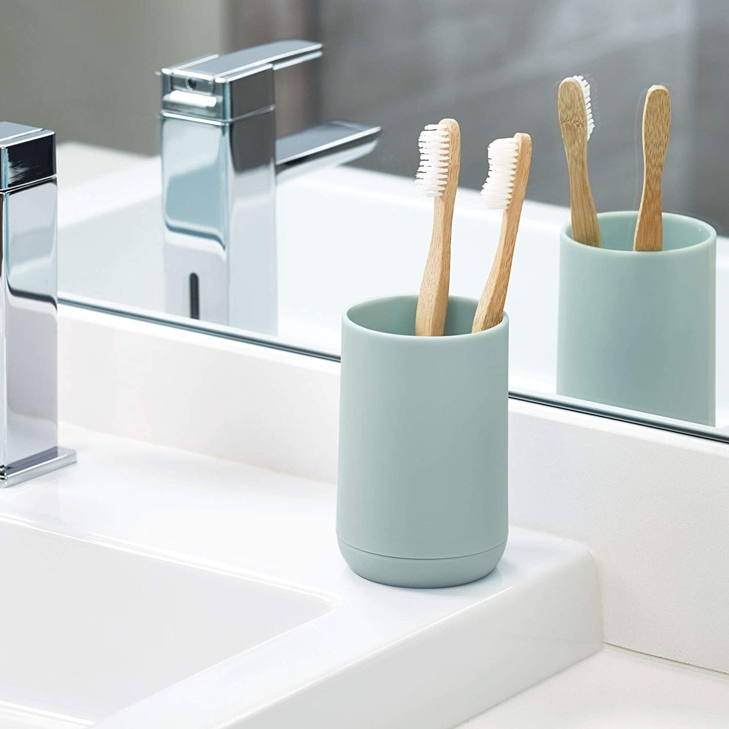 The toothbrush holder on a counter with two bamboo toothbrushes in it