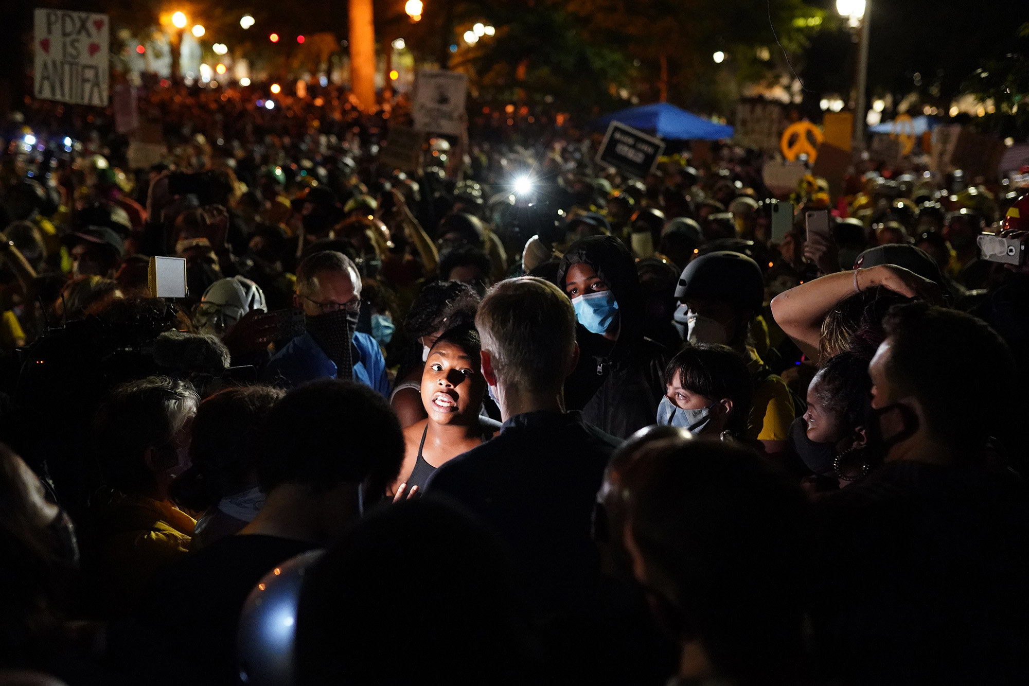A protester illuminated by a camera flash speaks with Portland Mayor Ted Wheeler surrounded by a large crowd