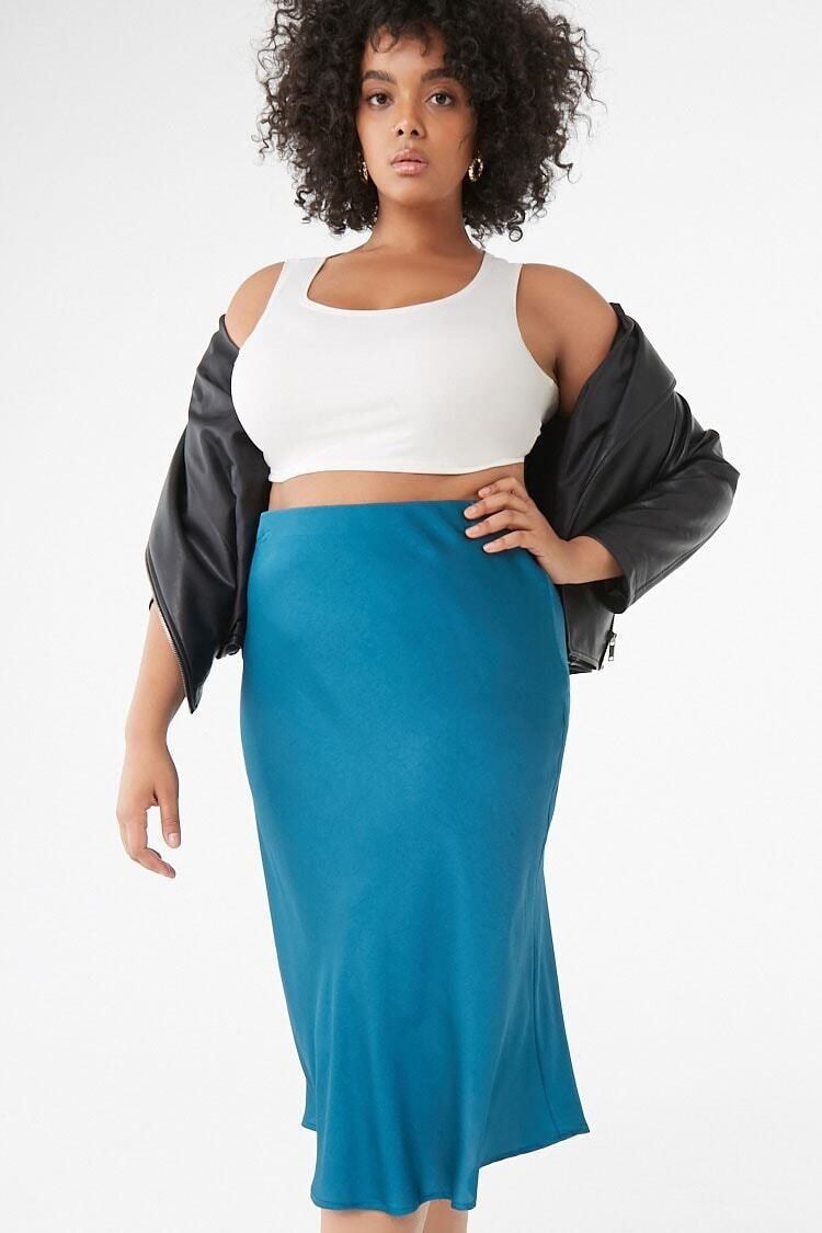 A model wearing the high-rise flowing skirt with a crop top and light jacket. The skirt hits right at the calf muscle and the top rises to the rib cage.