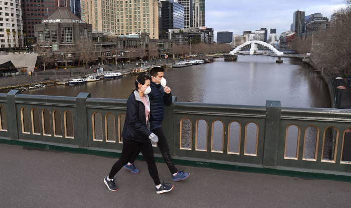 A man and woman wearing face masks and puffy jackets walk across a bridge on a river with tall city buildings in the background.