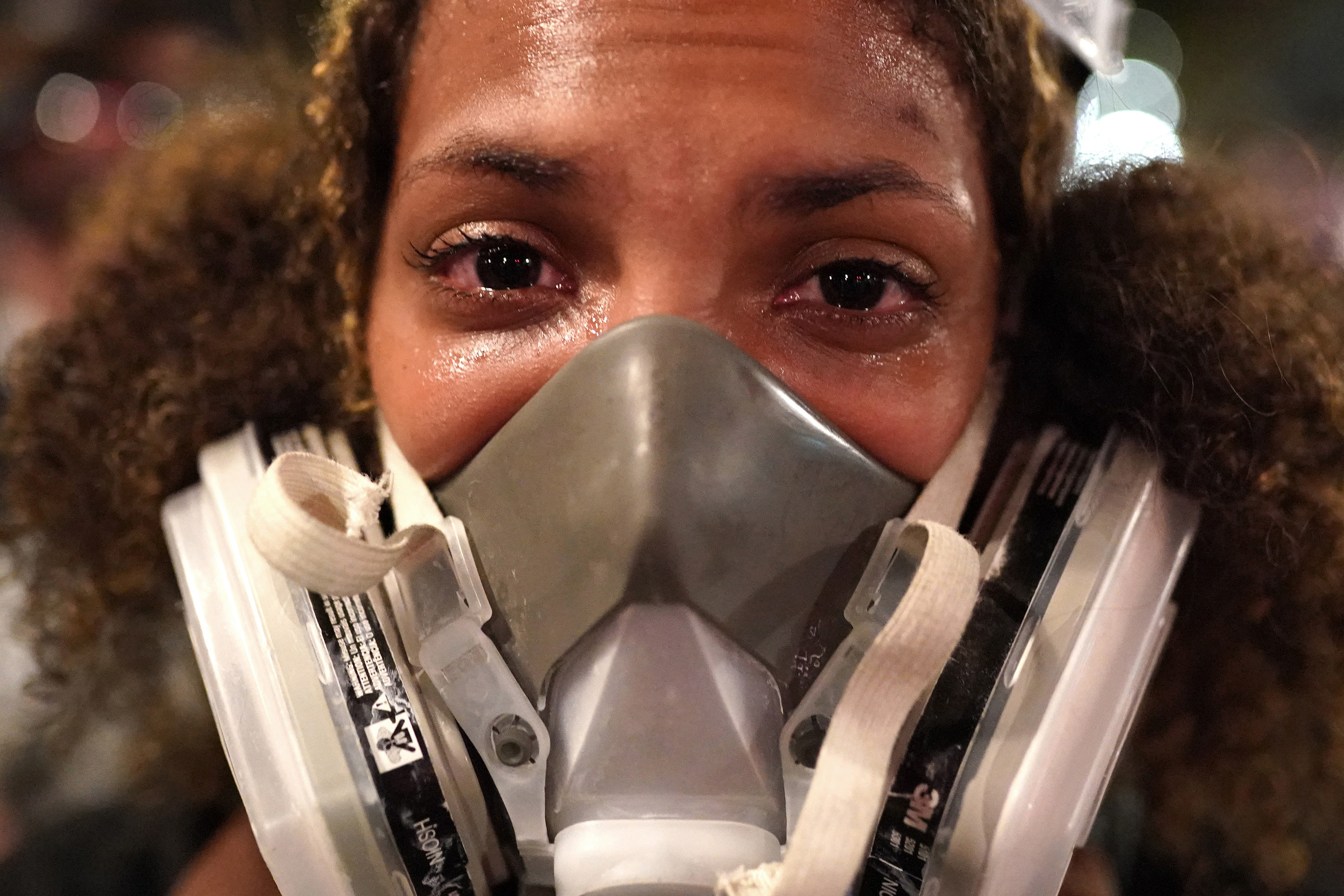 An extreme close-up of a woman wearing a mask as she reacts to tear gas and her eyes water