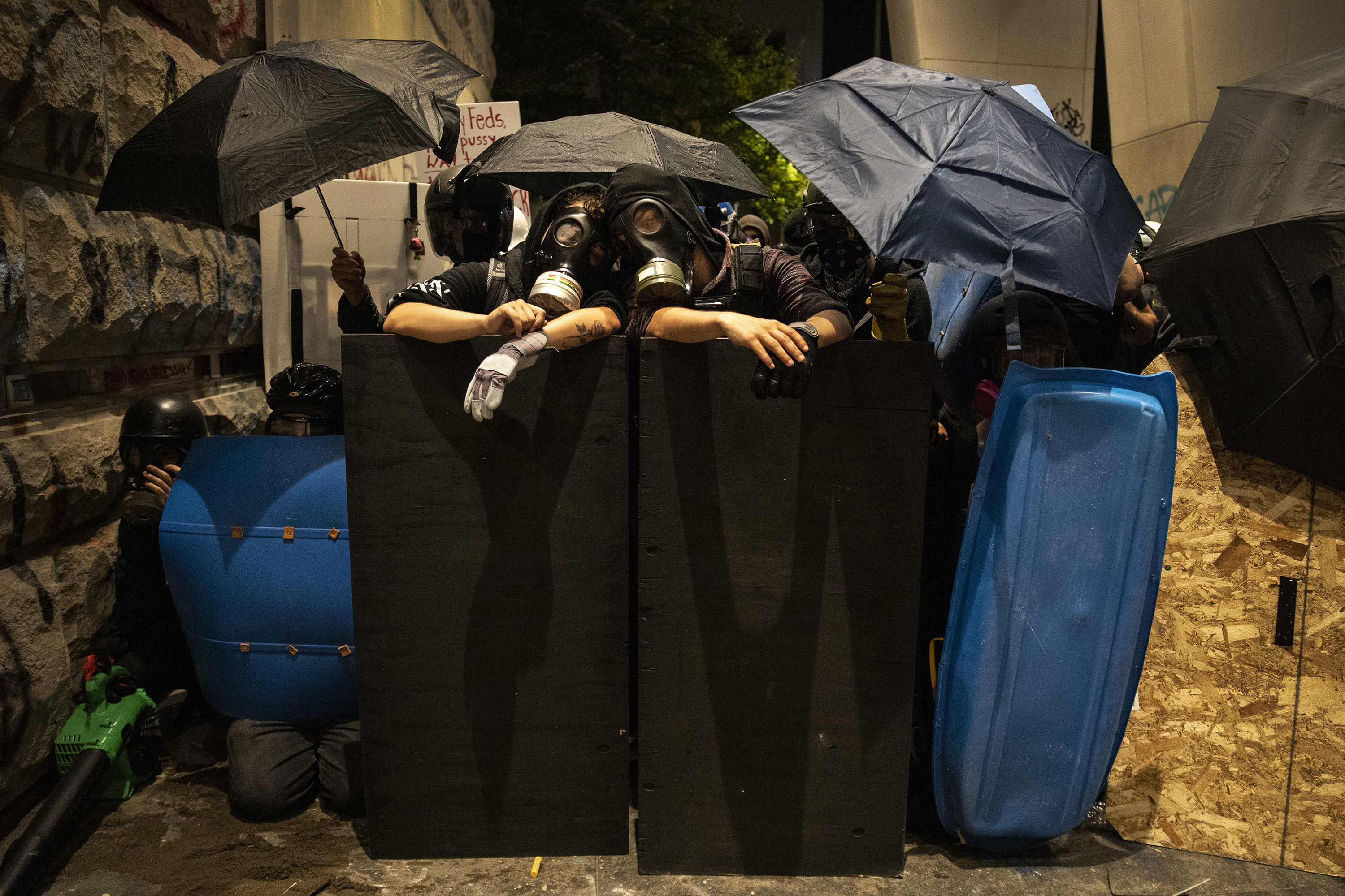 Protesters with gas masks rest against a homemade barrier during a demonstration in Portland