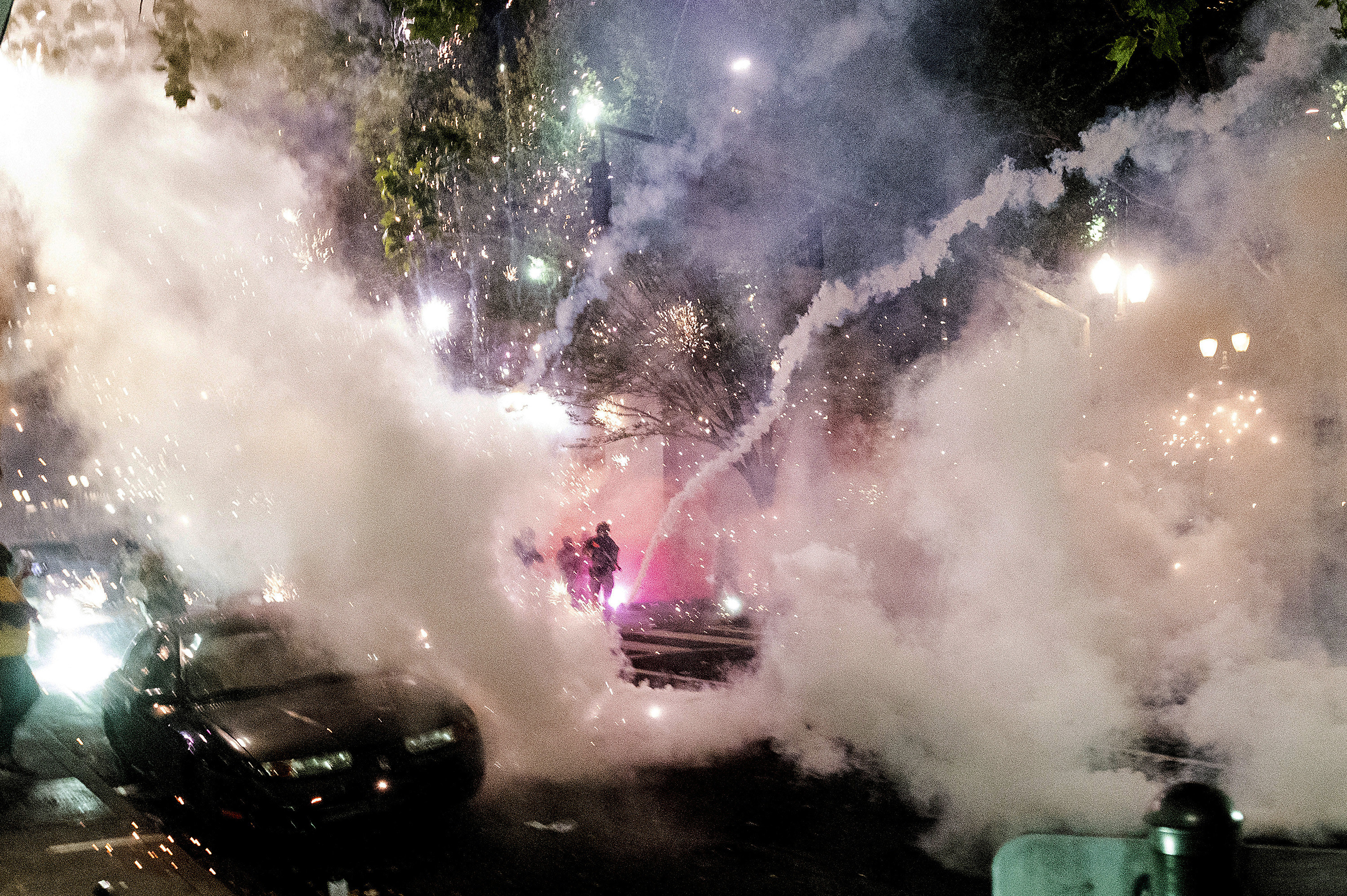 Smoke, tear gas, and sparklers fill the sky as federal officers advance to disperse protesters