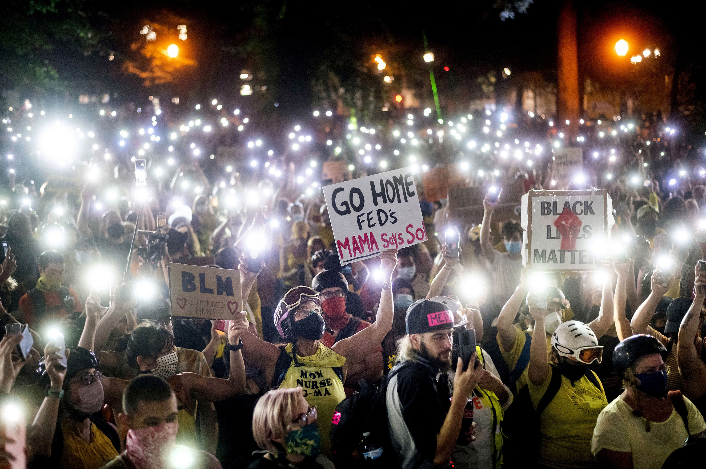 "Hundreds of Black Lives Matter protesters hold their phones aloft creating a sea of flashlights. Signs in the crowd read ""BLM"" and ""Go Home Feds. Mama says so!"""