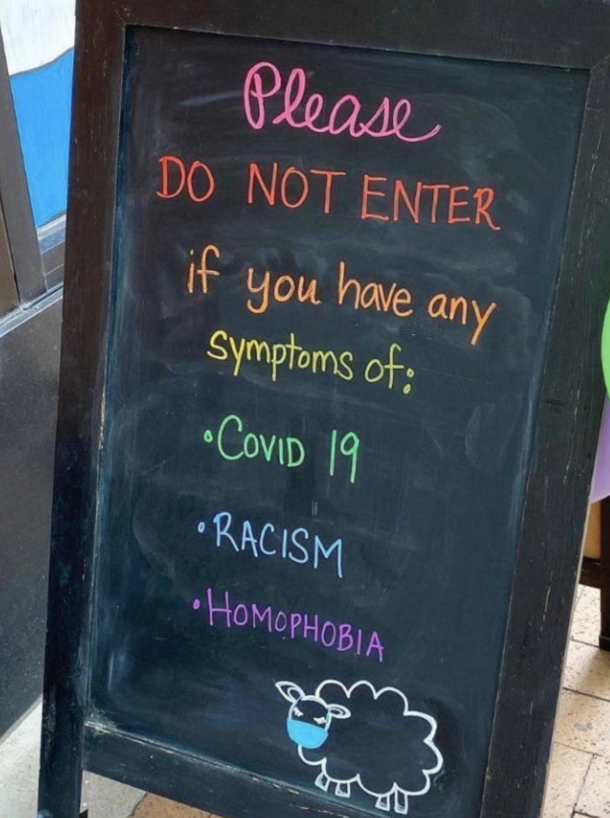 Sign reading please don't enter with symptoms of covid-19, racism, homophobia