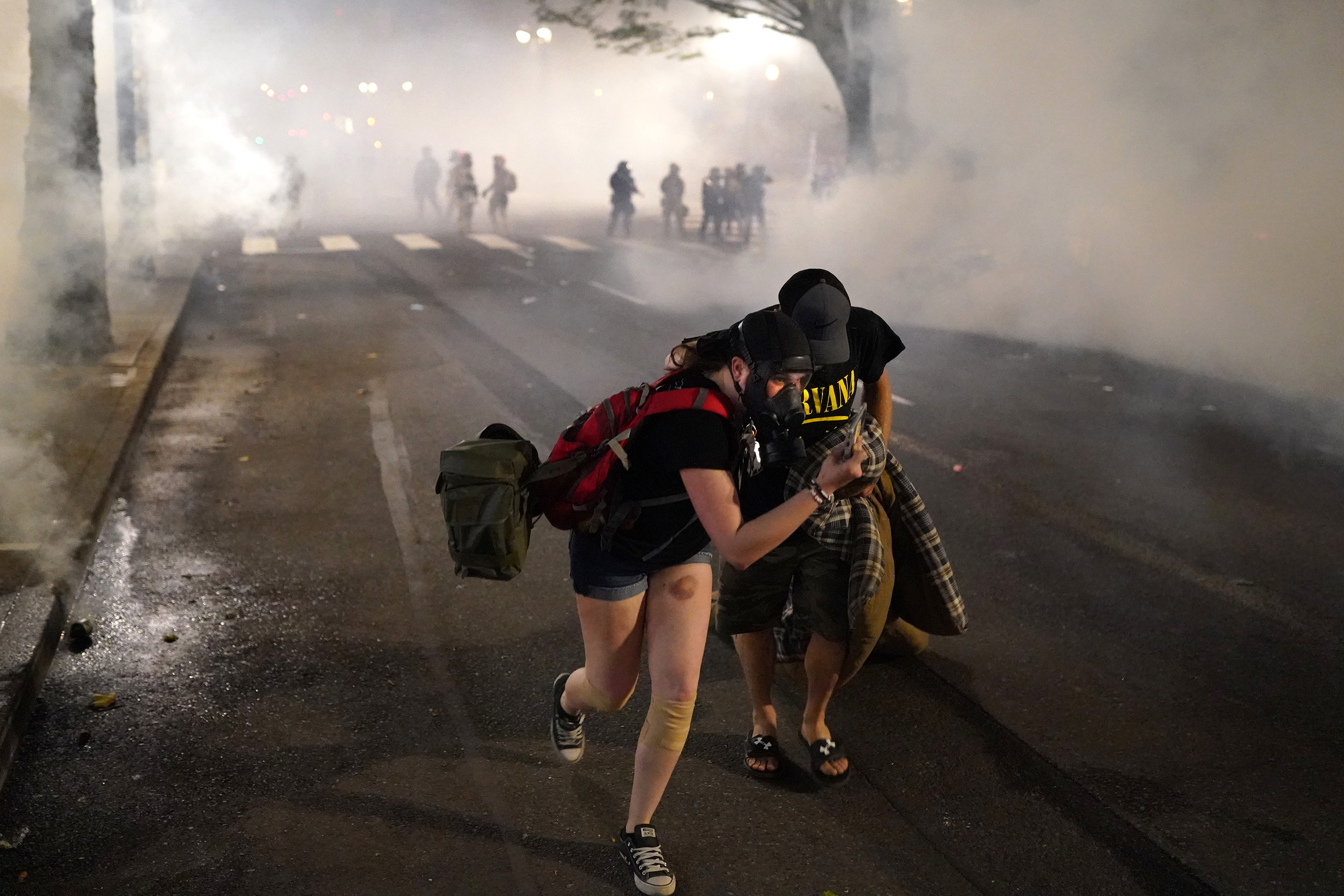 Two protesters flee through tear gas after federal officers dispersed a crowd using tear gas in Portland