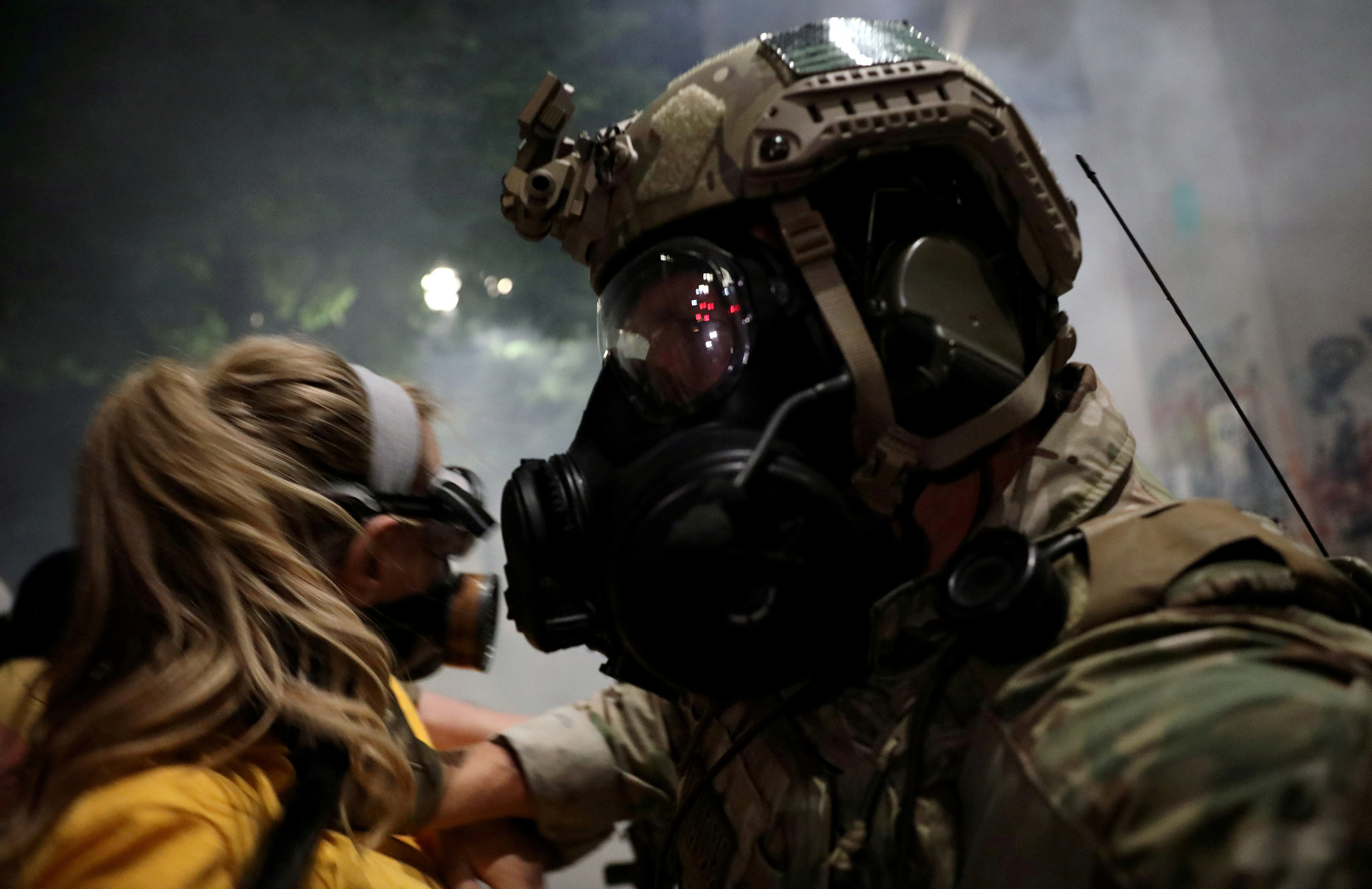A woman in a yellow shirt and face mask faces off with a federal law enforcement officer, who pushes her back
