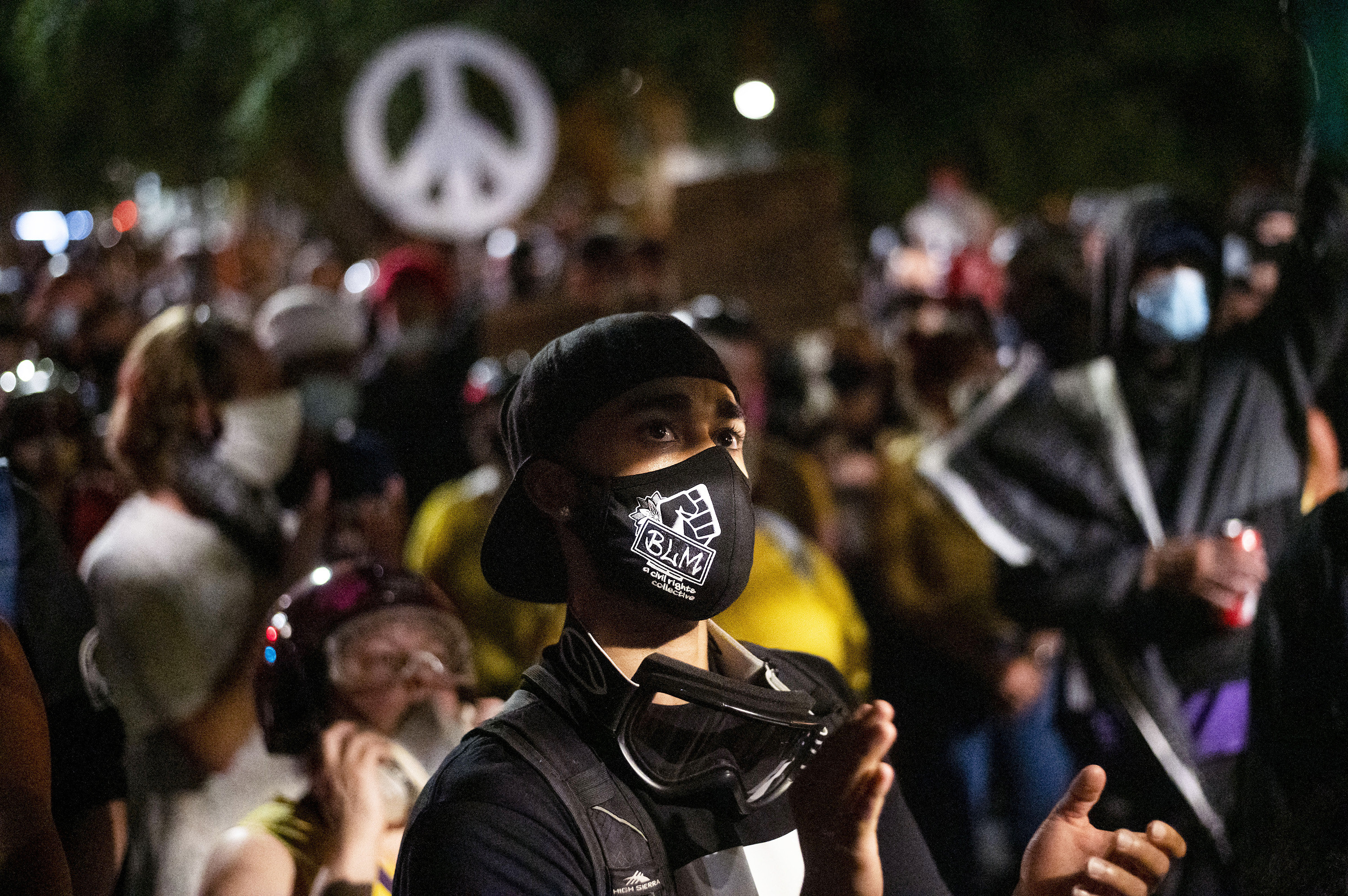 "A protester in a black mask that reads ""BLM"" applauds as they stare off camera"