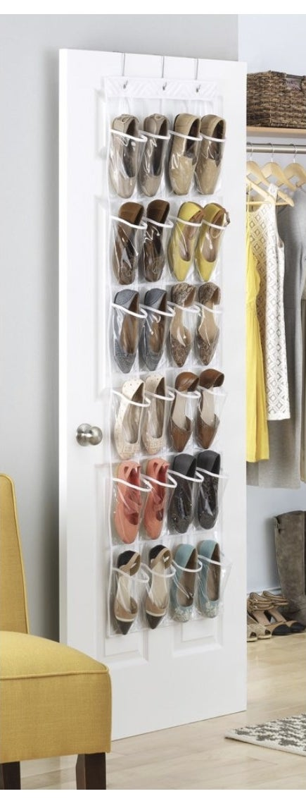 A plastic clear shoe organizer hanging from a closet door