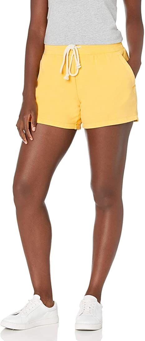 model wearing bright yellow fleece shorts with a drawstring