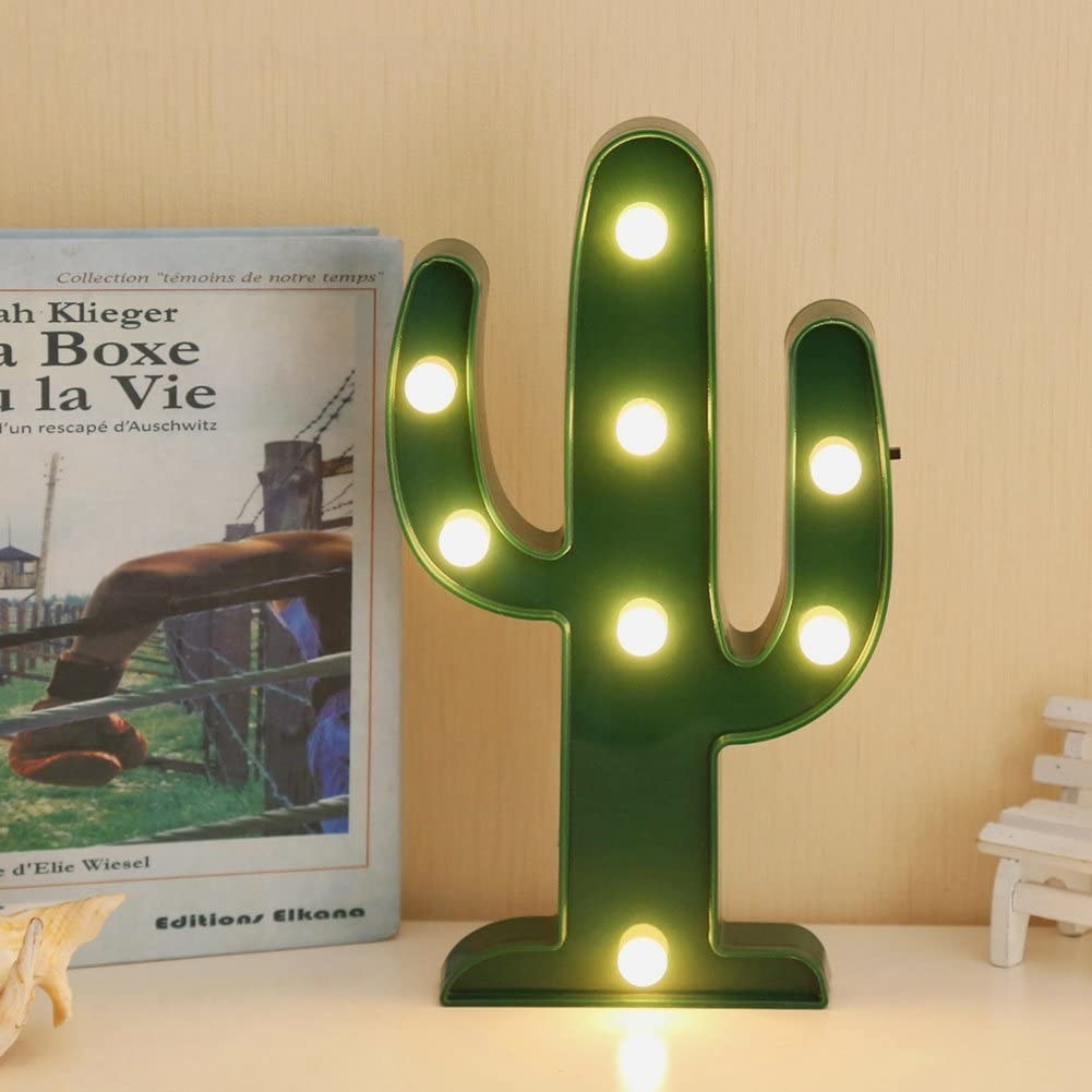 A small night light in the shape of a cactus There are eight lights spread out along the stem and the shoots of the cactus