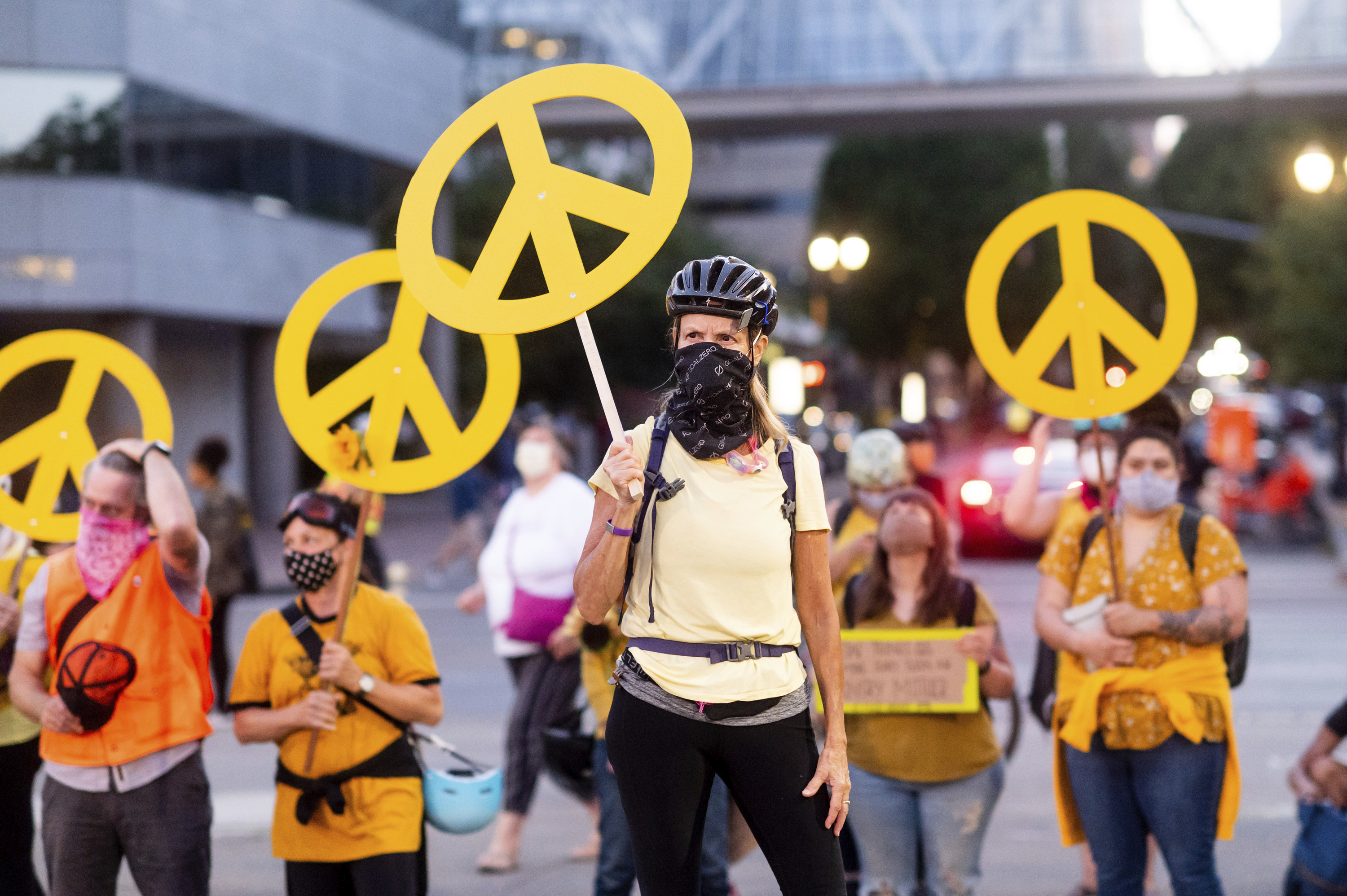 A woman holds a yellow peace sign with others in the crowd wearing matching yellow shirts doing the same during a protest