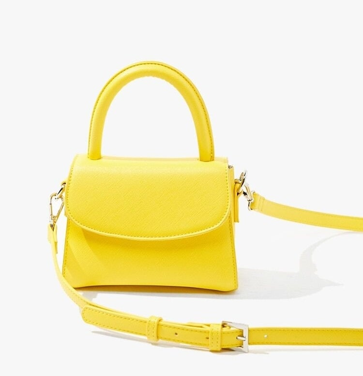 A tiny, bright yellow purse with a flap closure, large structured handle, and metal buckle details on the long strap