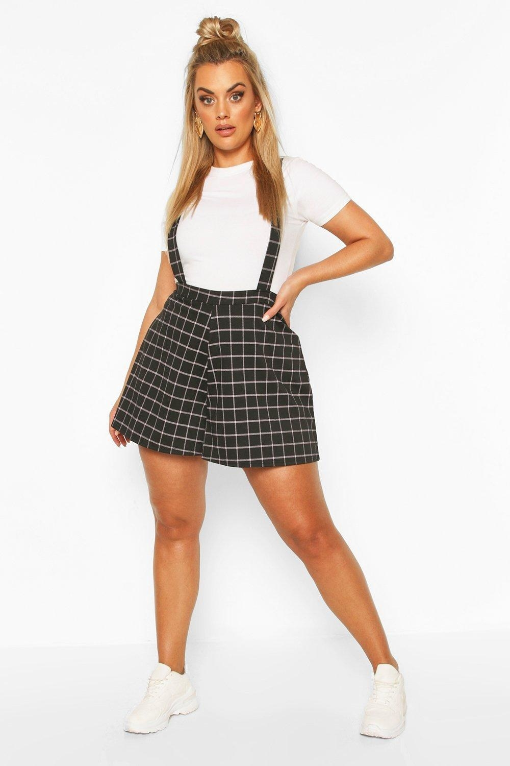 model wearing check print black pinafore shorts with straps that go up on shoulders