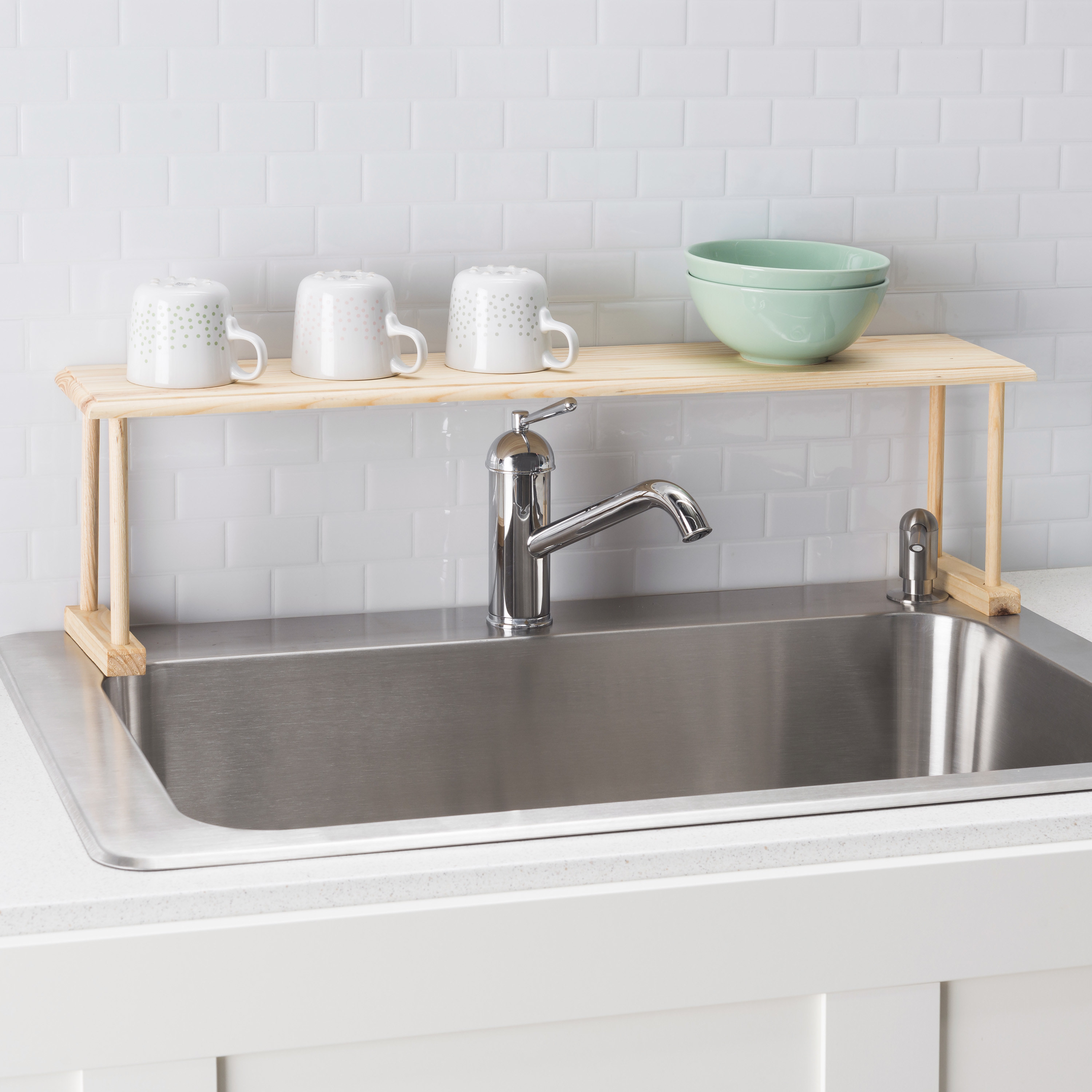 A light wood over the sink shelf with dishes on it
