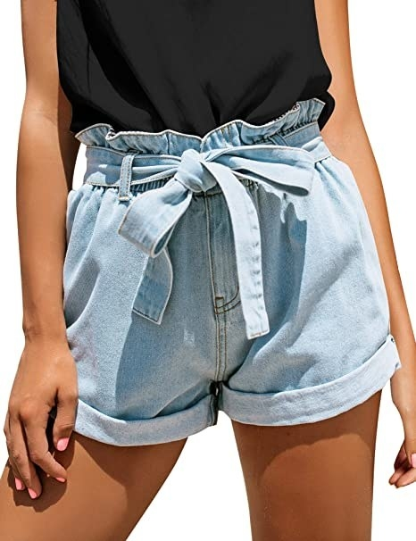 model wearing light denim high rise shorts with paperbag top and tie belt