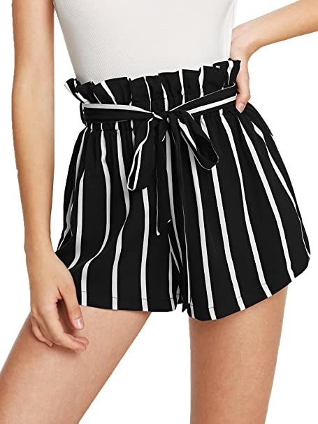 model with paperbag waist shorts with tie belt and black background with white stripes