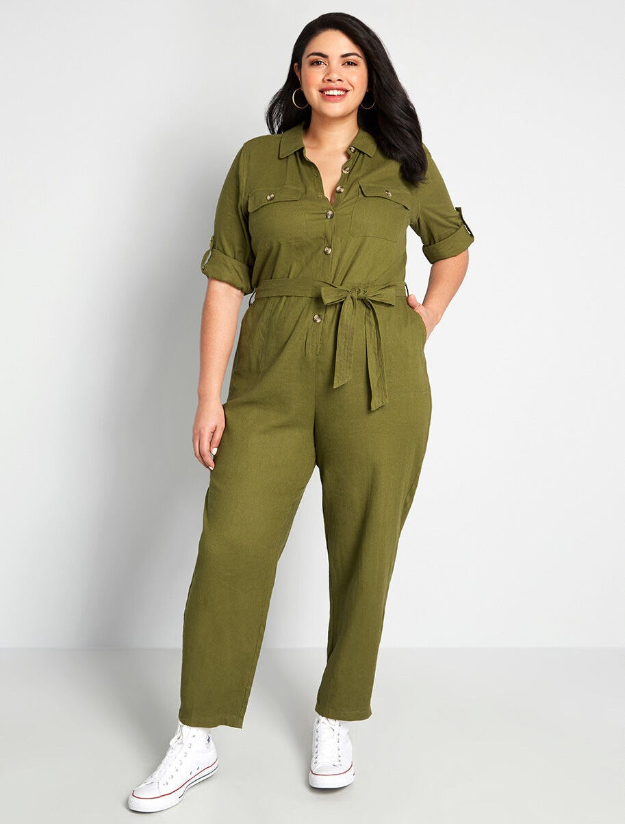 Model wearing the jumpsuit in green, featuring front button closures, slim fit legs, a sash-tied waist, and pockets