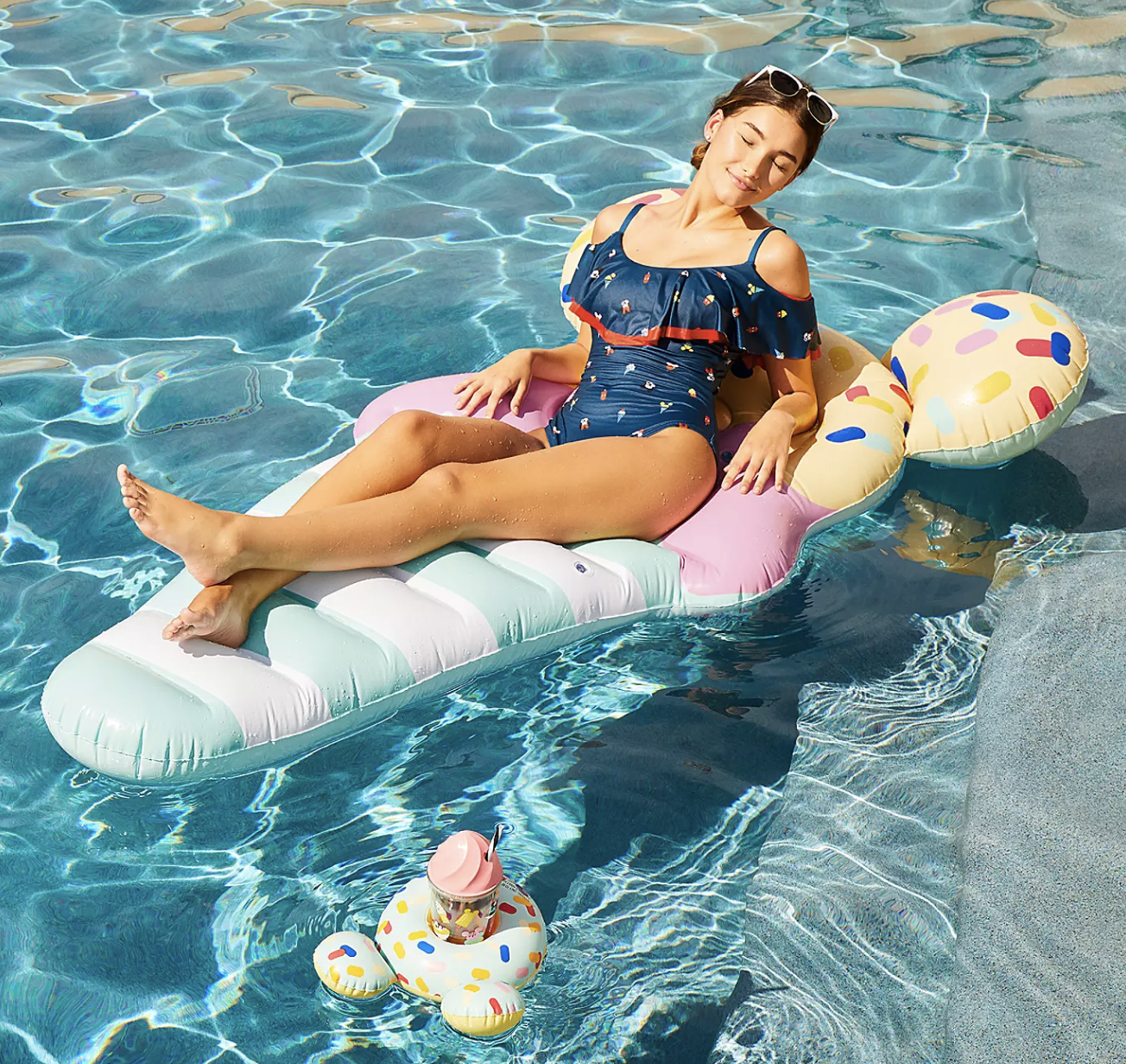 A model on an ice cream Mickey Mouse pool float