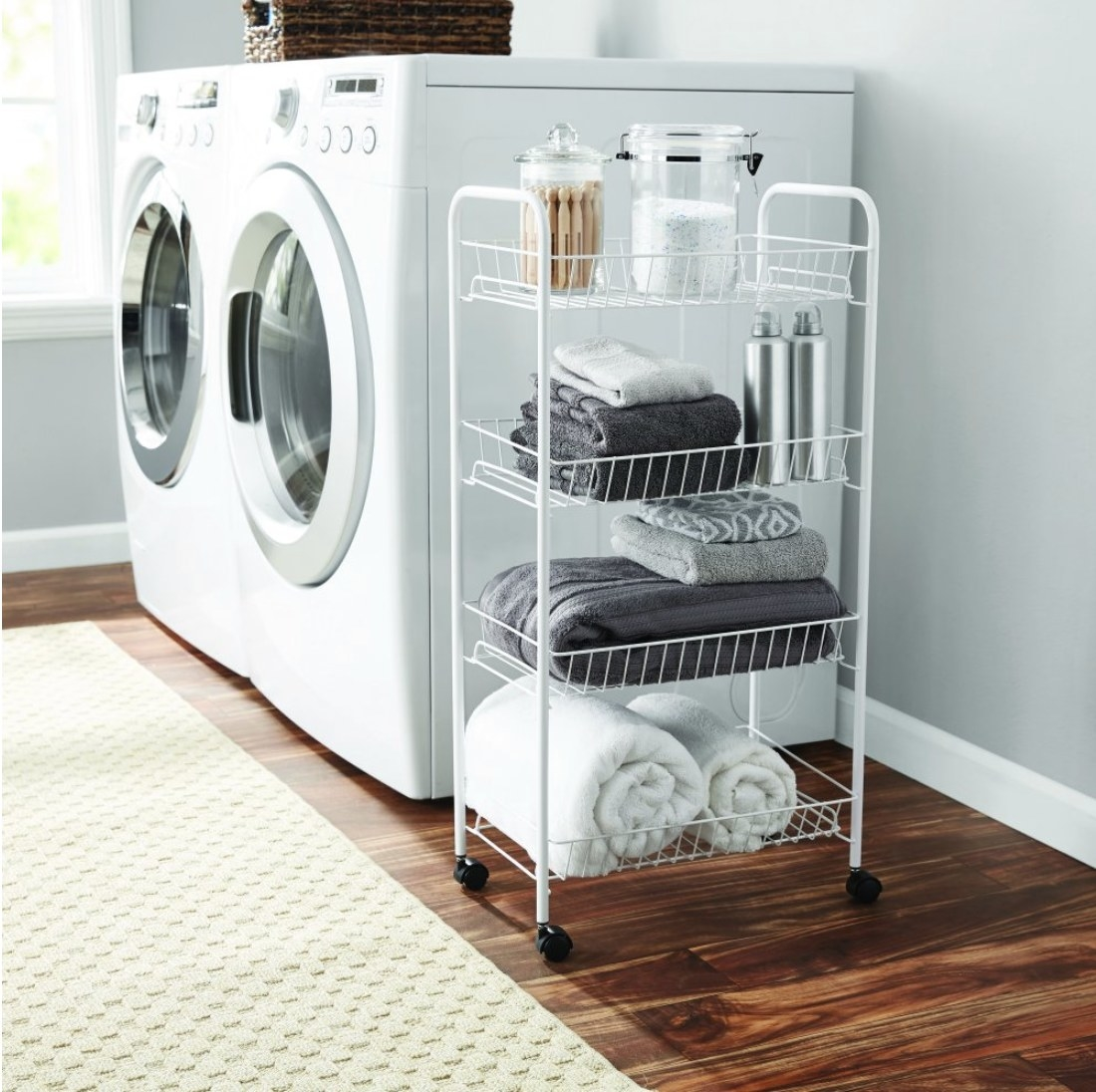 The white four tier wire cart in a laundry room