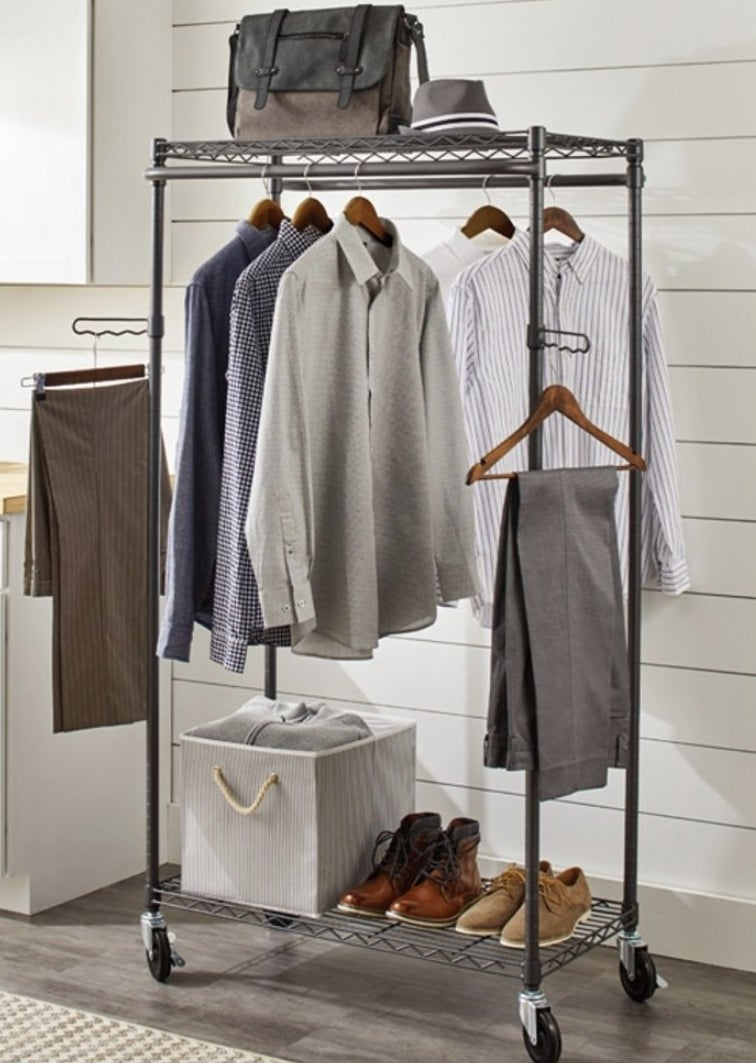 A metal garment rack with a bottom shelf