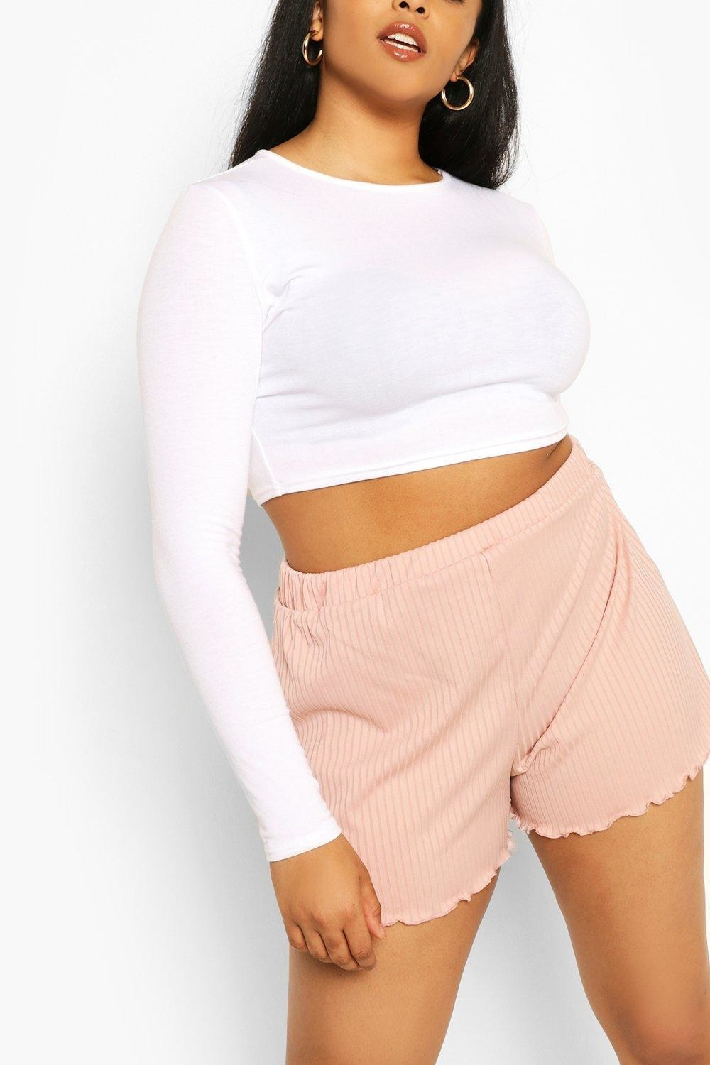 modeel wearing white crop top and blush ribbed shorts with a lettuce ruffle hem