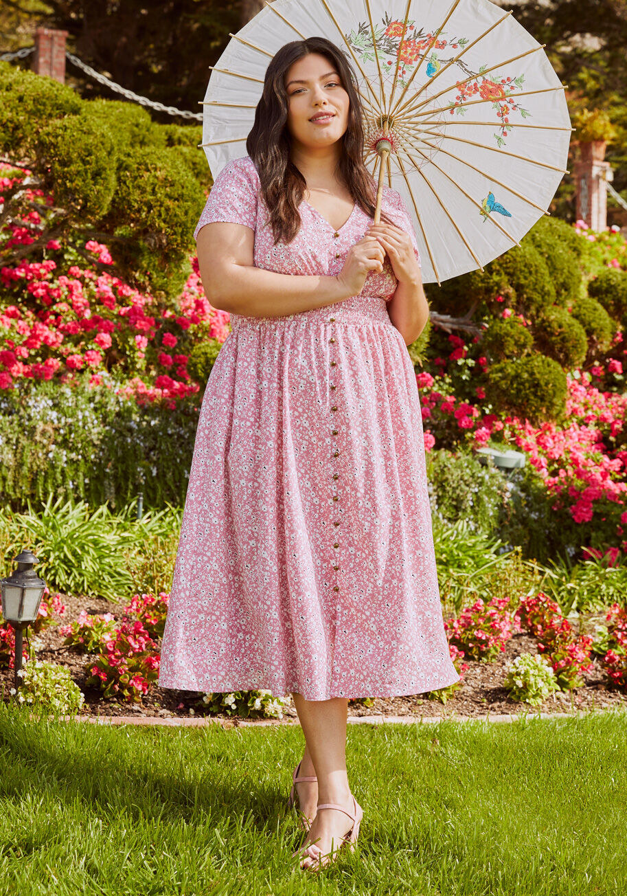 Model wearing the dress in pink floral, featuring a v-neck, smocked waist, and gold buttons down the front