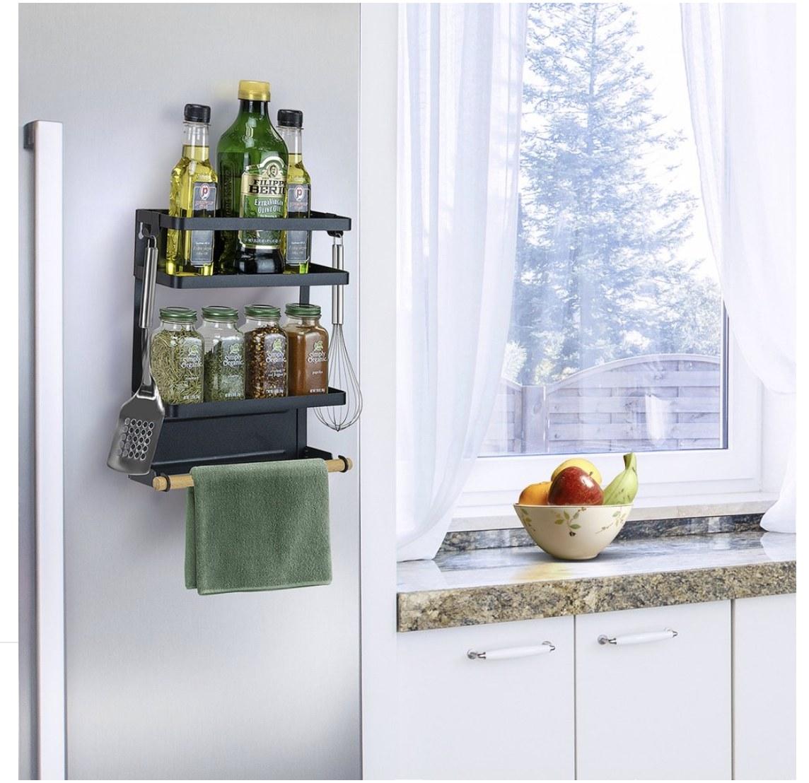 A spice rack shelf hanging from a fridge