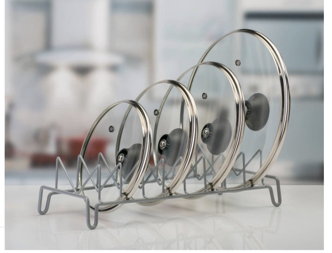 A metal lid shelf with four lids stacked in it