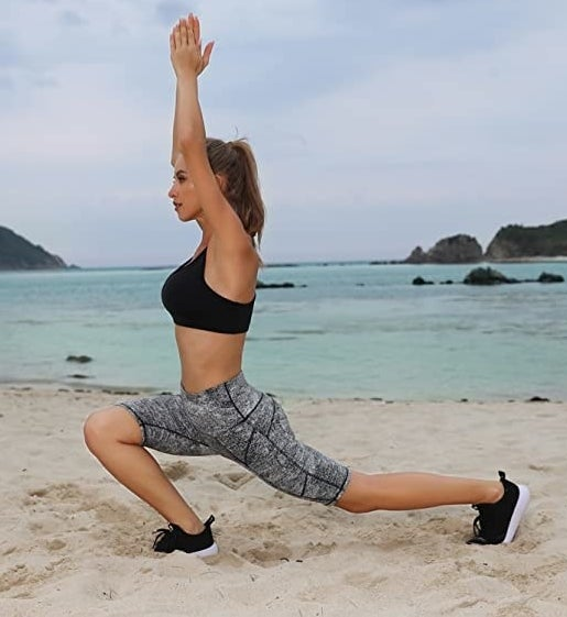 model wearing the tight-fitting stretchy light gray shorts that are high rise and go to knees while doing yoga on a beach