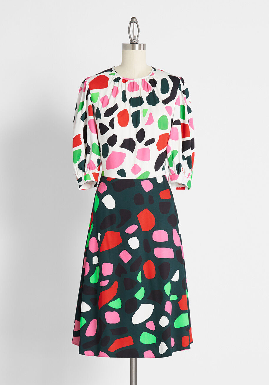 The dress, featuring a contrasting bodice and skirt covered in colorful blotches of color, a high neckline, and puffed sleeves