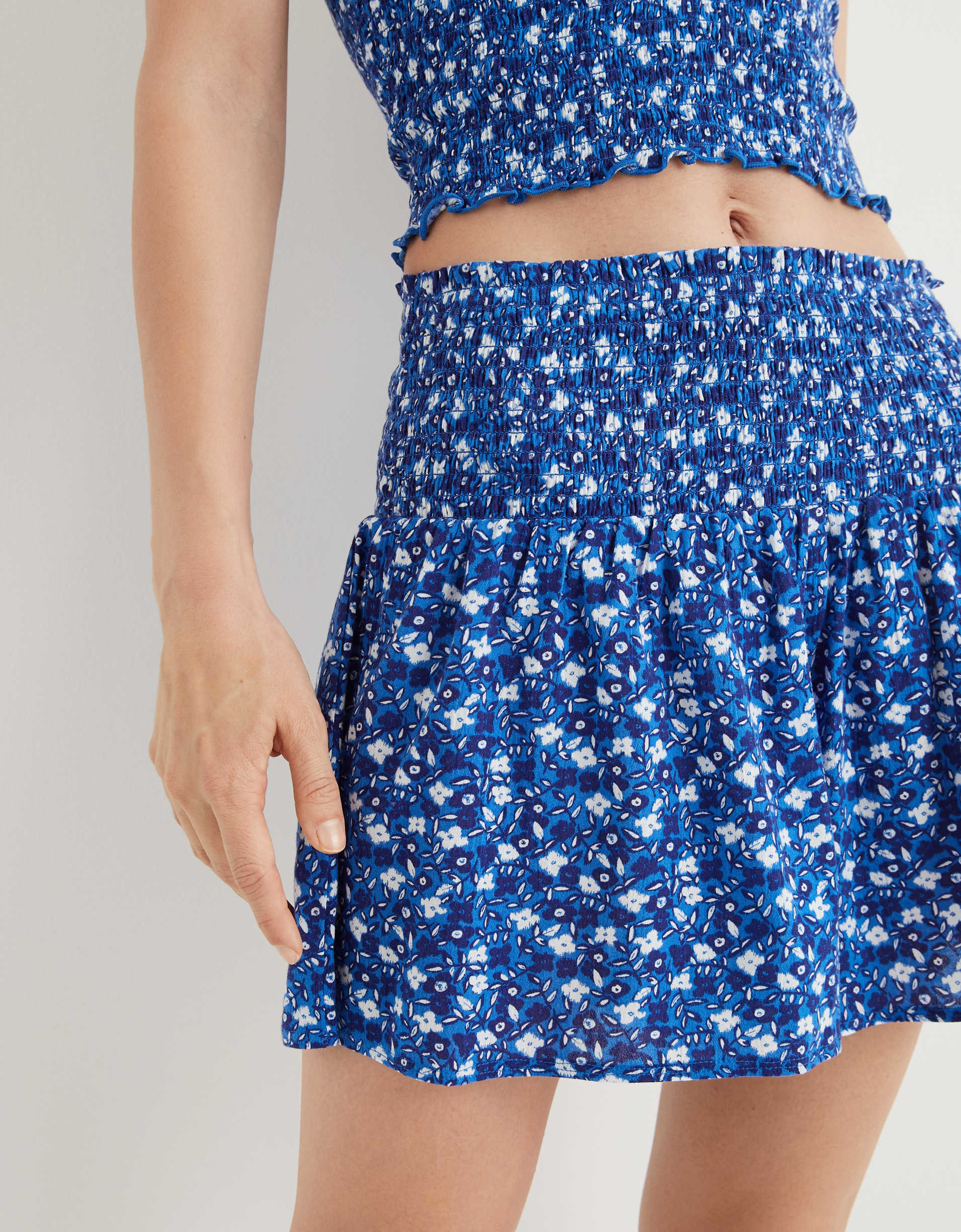model wearing blue floral crop top and match smocked waist shorts