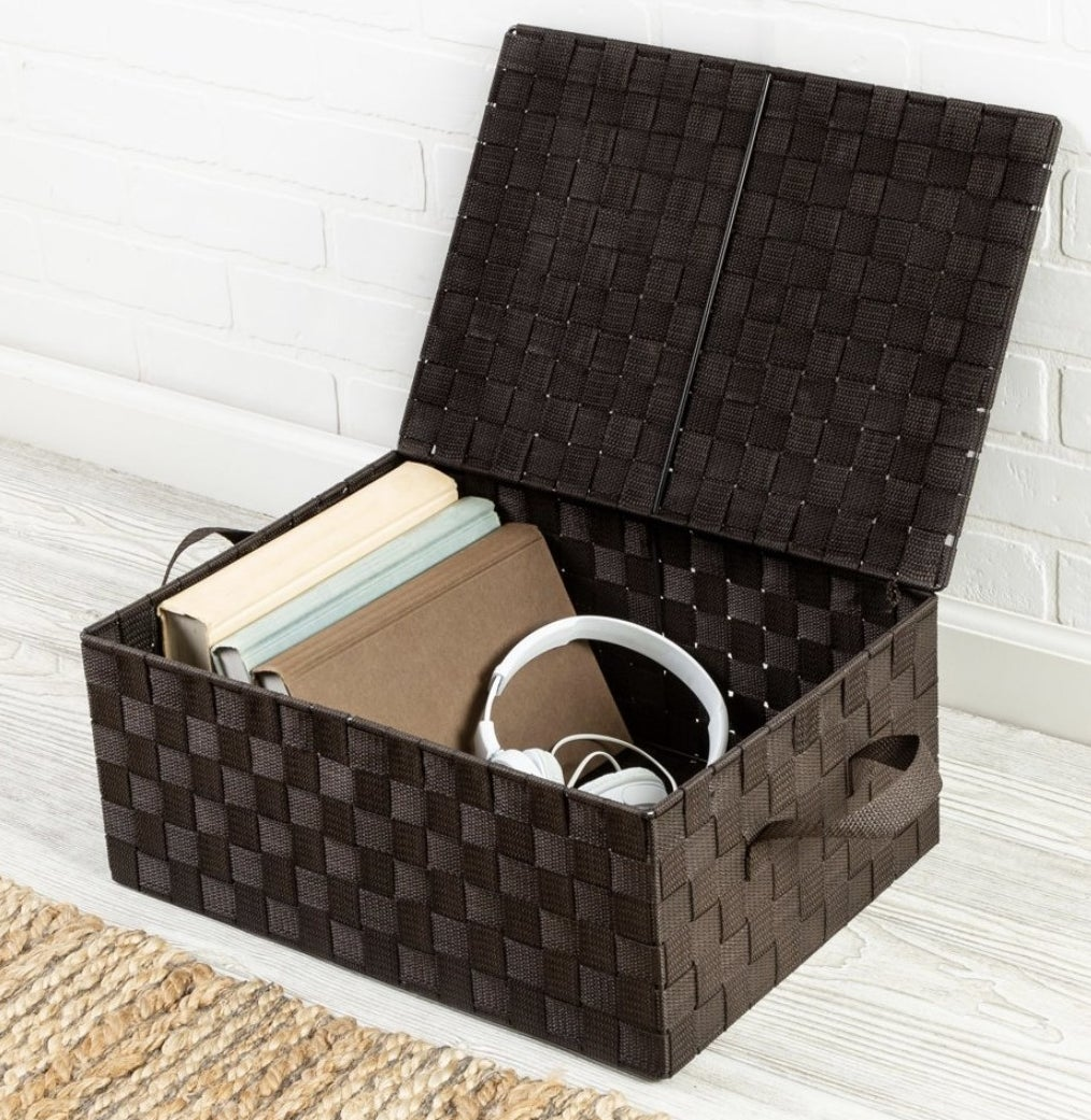 A dark brown woven storage box with a flip lid