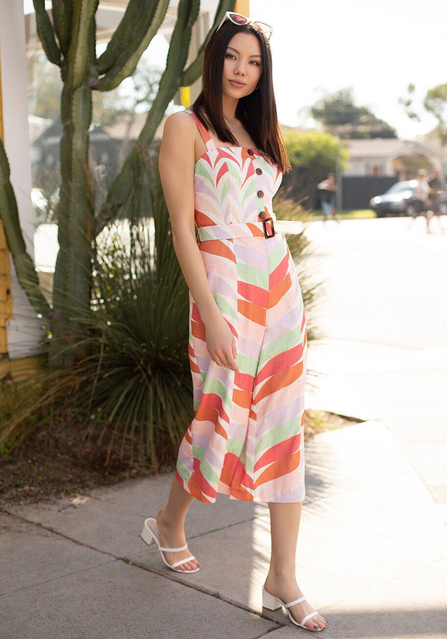 Model wearing the jumpsuit, featuring fixed wide shoulder straps, a buttoned bodice, cropped, and wide legs