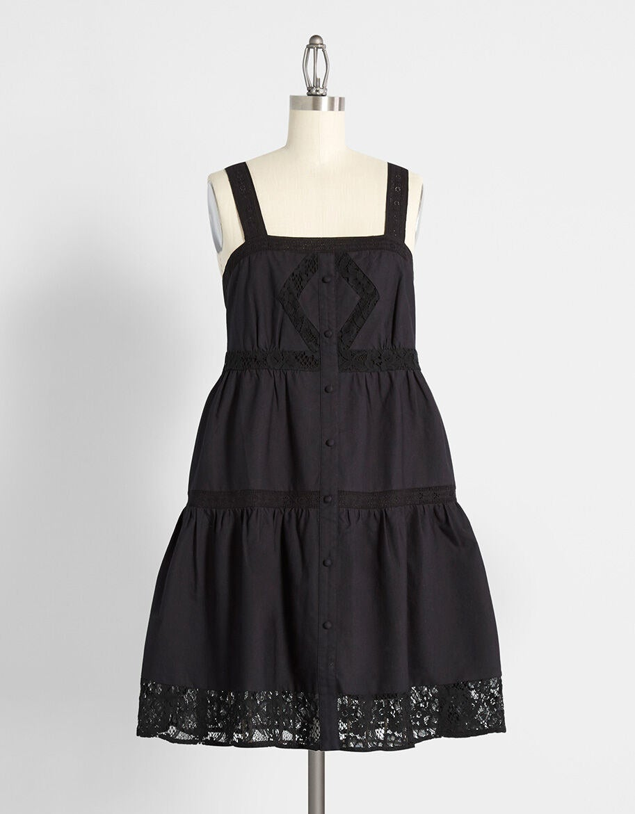 The sleeveless dress featuring back smocking, floral lace insets, and tiered design