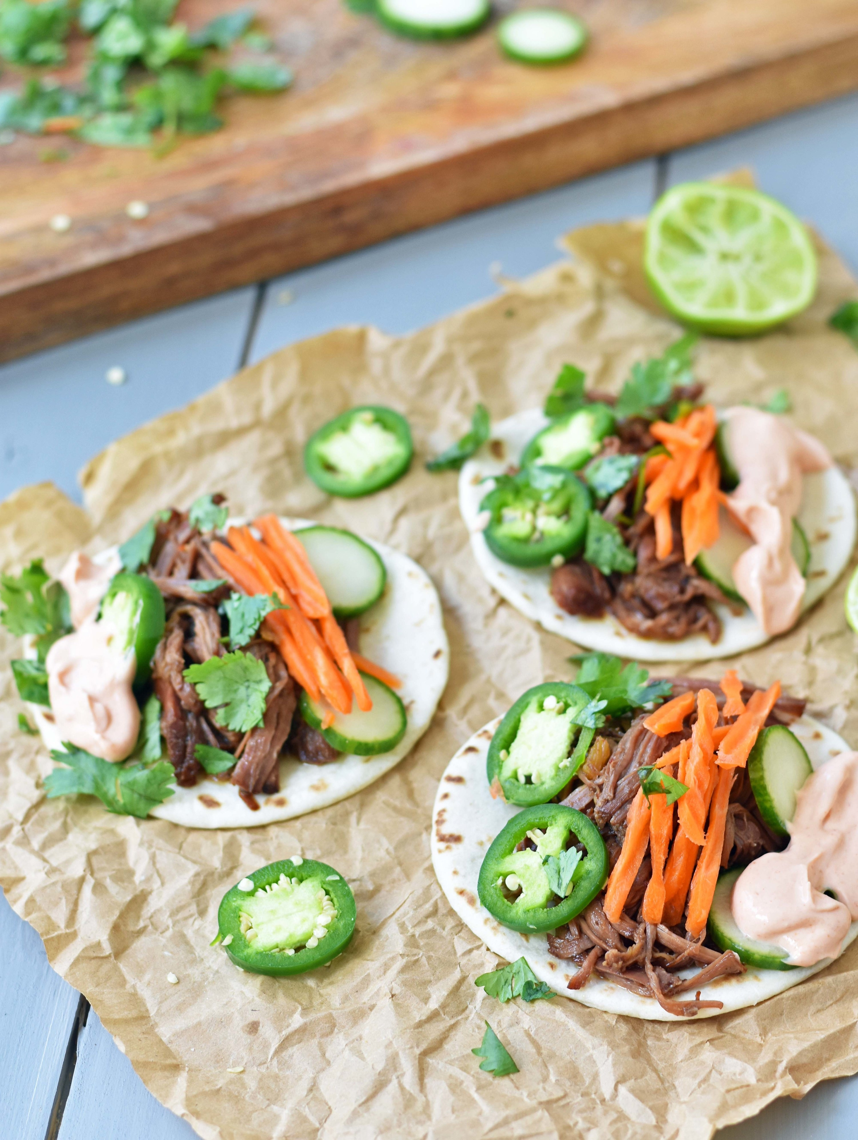 Three flour tortillas topped with Korean beef, jalapenos, matchstick carrots, and mayonnaise.