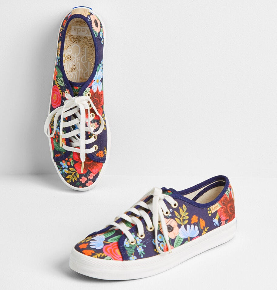 The lace-up sneakers, featuring a colorful floral design on a navy background