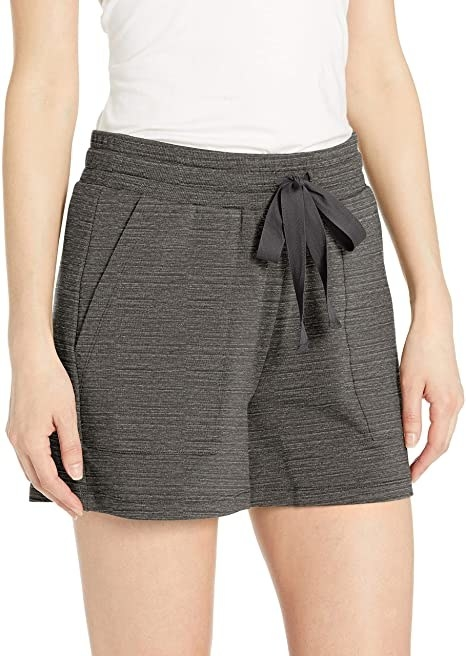 model wearing dark gray soft shorts with a pocket and drawstring waist