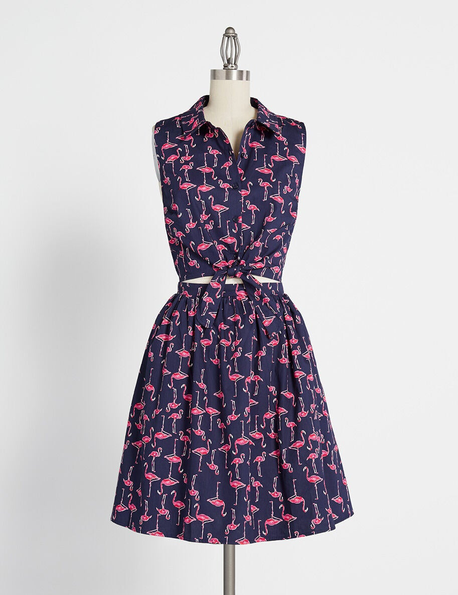The dress in navy, featuring row of buttons down the top, with a gap between the bodice and the skirt