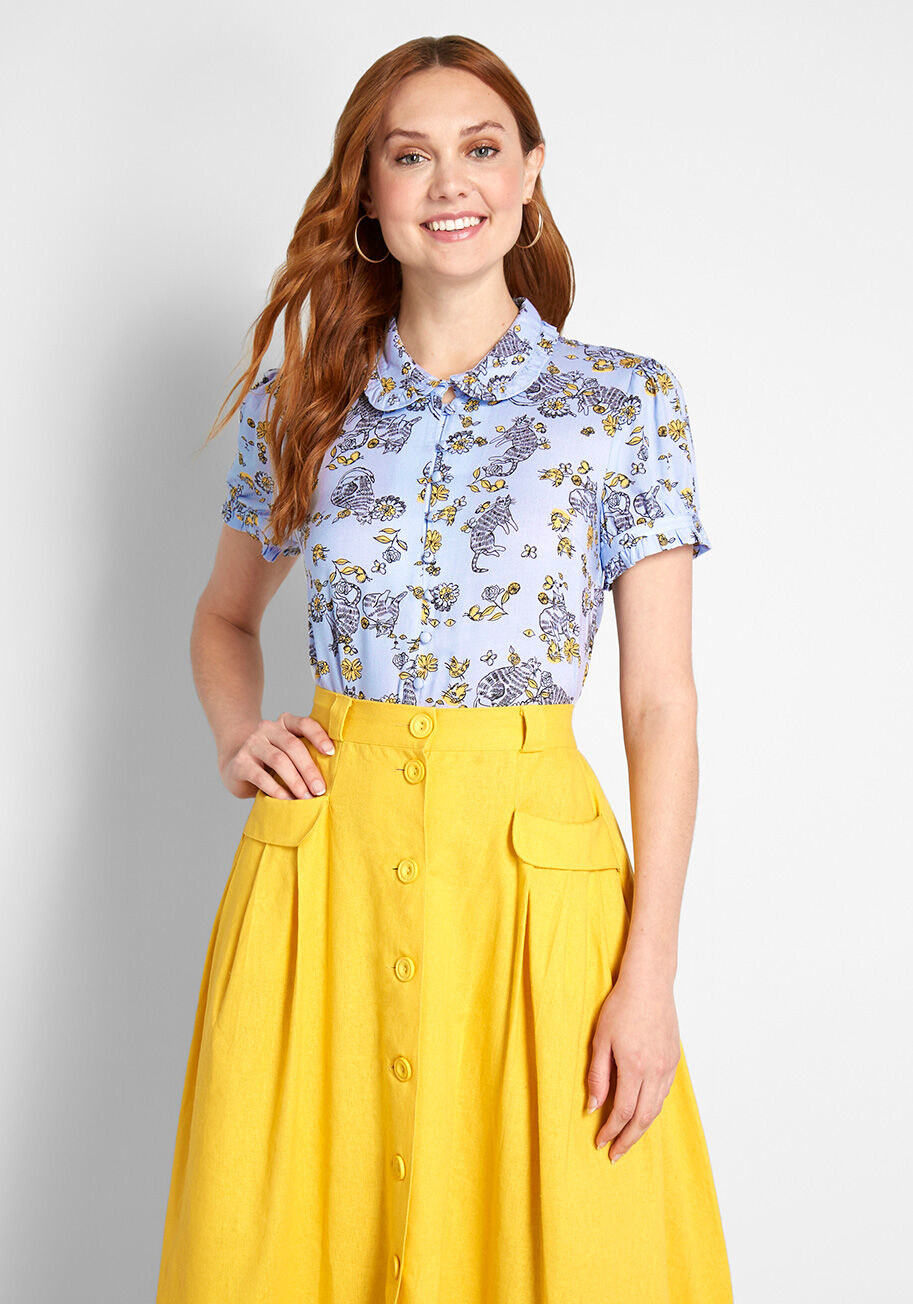 Model wearing the button-down blouse, featuring a ruffled, rounded collar and coordinating short sleeve cuffs