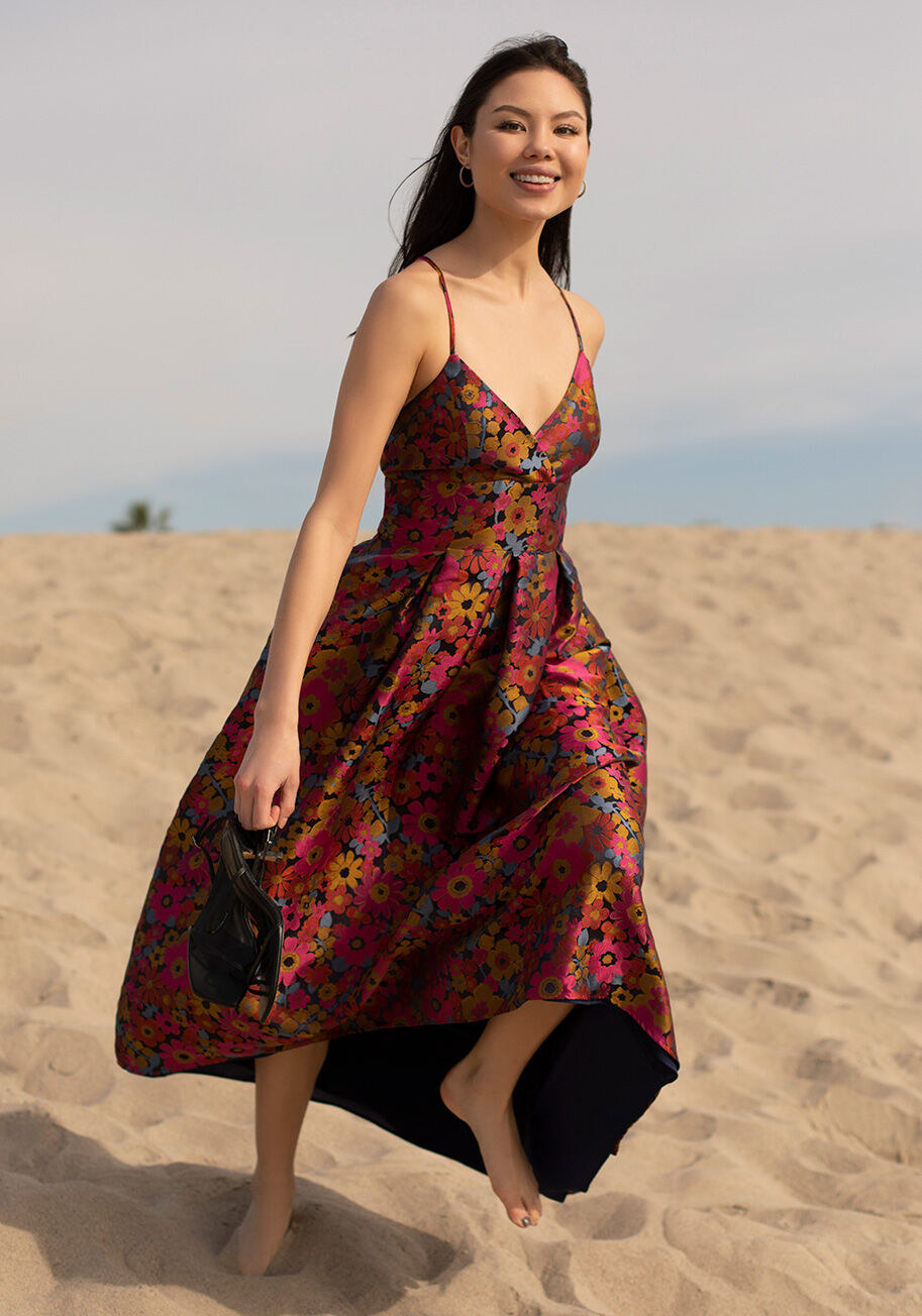 Model wearing the gown, featuring a floral pattern, crossback straps, and low neckline