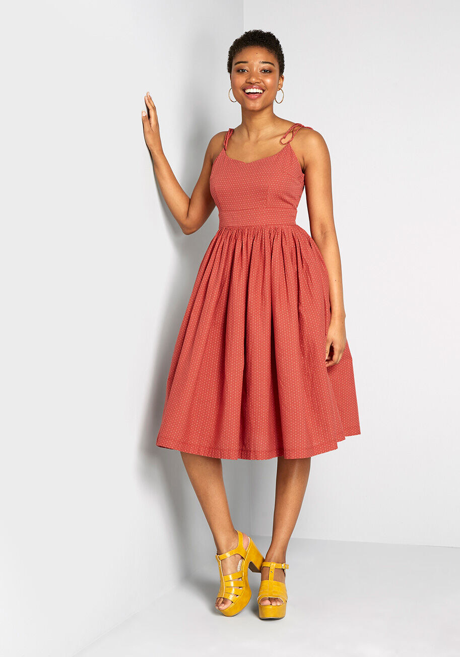 Model wearing the midi dress in orange, featuring a fit-and-flare silhouette, V-neckline, and dot pattern