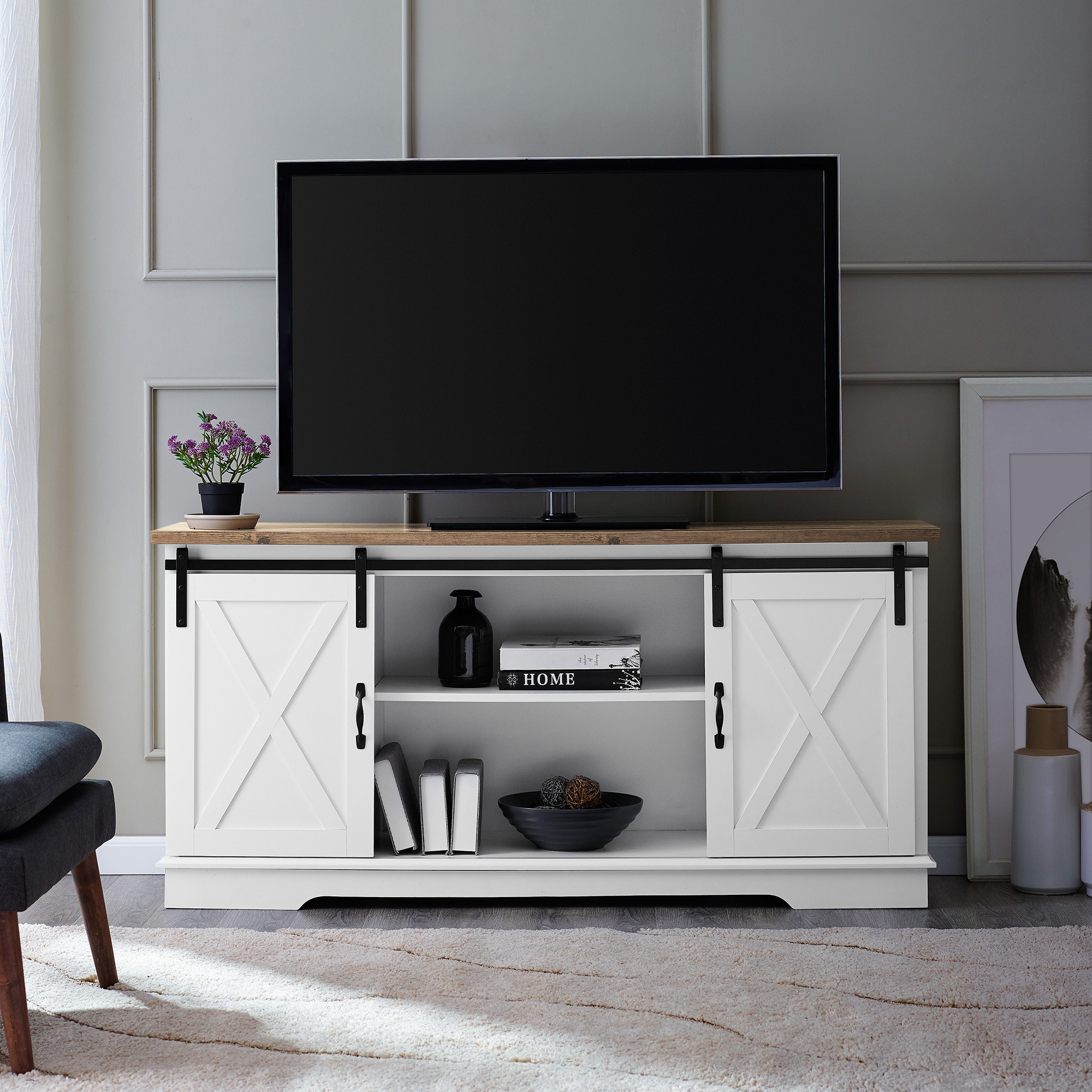 A white wood TV stand with two shelves and two cabinets