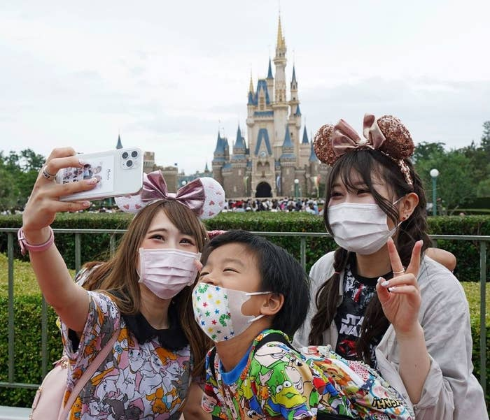 Three people pose for a selfie wearing face masks and ears in front of the Disneyland castle in Tokyo.