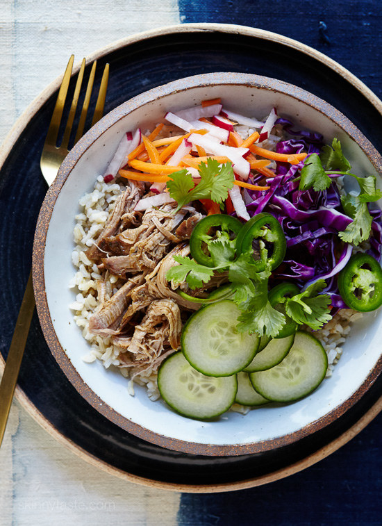 A bowl with rice, shredded pork, sliced cucumbers, cabbage, carrots, jalapeno, and cilantro.