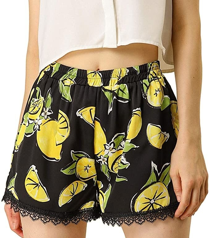 model wearing black high waist shorts with cartoon lemon print on them and lacey trim