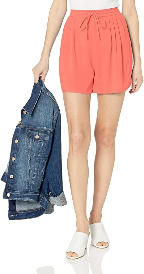 model wearing coral pull on shorts with a drawstring