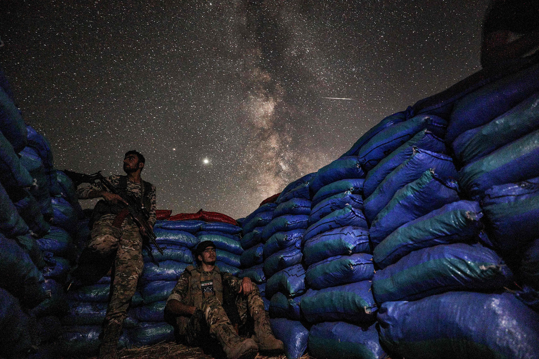 Two Syrian soldiers, one sitting on the ground and the other standing, are surrounded by sandbags that form a barrier; above them, the Milky Way galaxy and many stars are visible