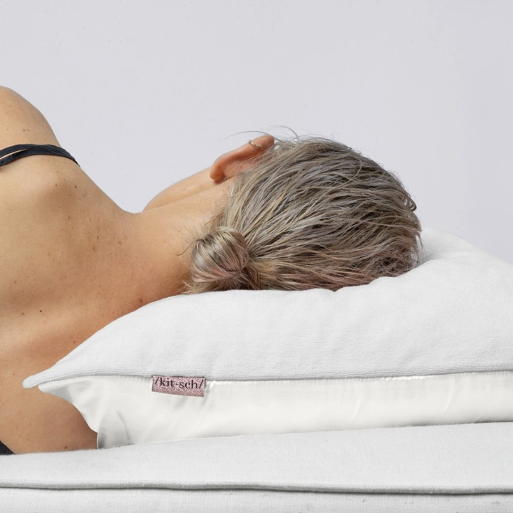 Model laying her head on the pillow with wet hair
