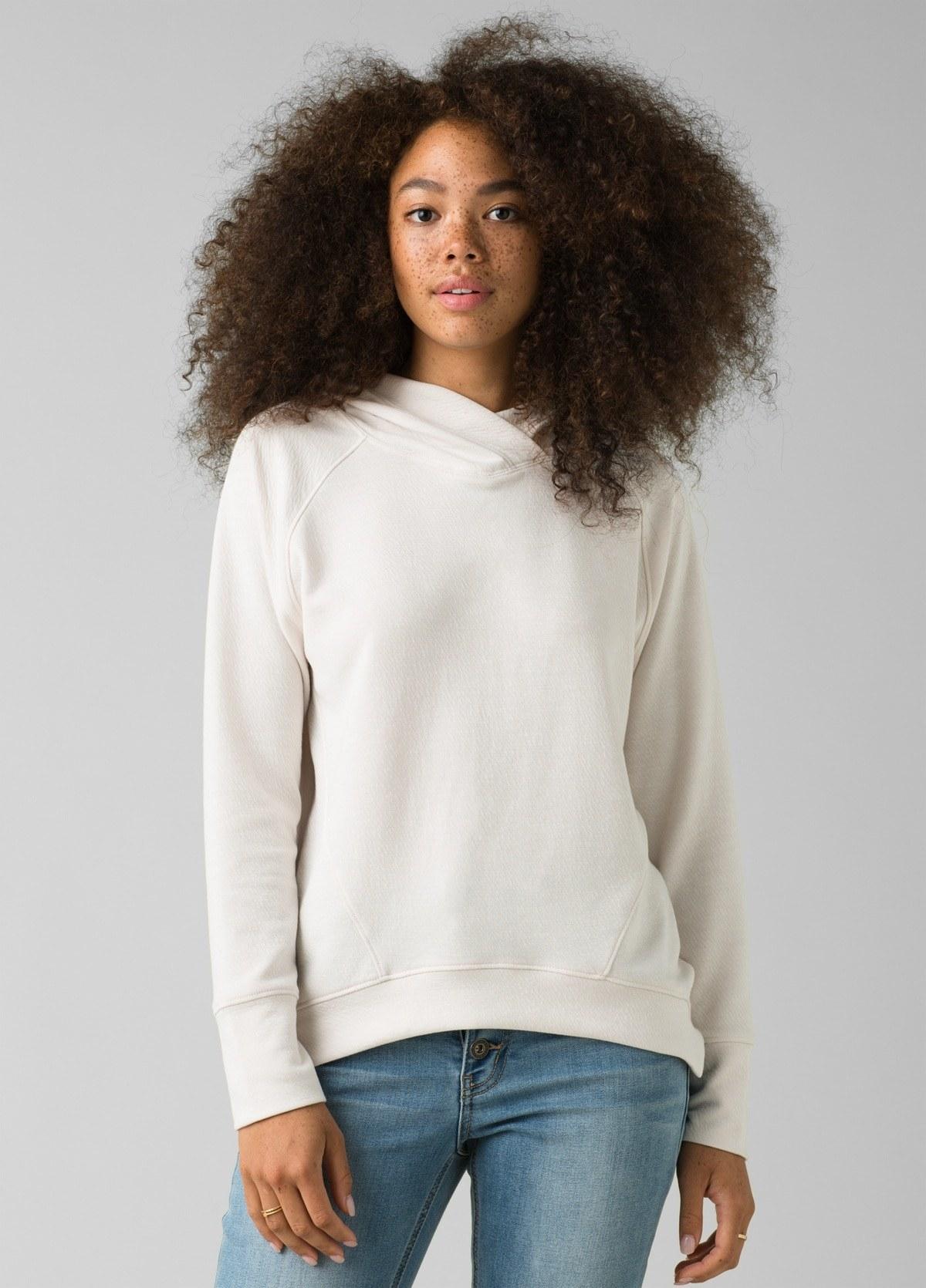 model in white hoodie with a slightly upward curving hemline